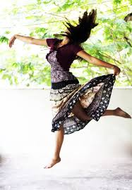 Woman in a short dress dancing against leaves and trees