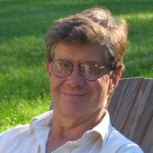 Photo of a middle aged white man with glasses sitting in a wooden chair out on a grassy lawn