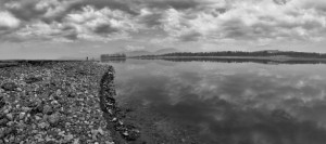 Rocky lake shore and clouds, black and white artistically balanced nature shot