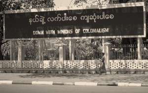 Sign reads: Down with the Minions of Colonialism in Burmese and English