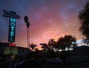 Motel sign lit up at dawn or dusk, city street with two palm trees and pink and purple sky