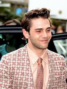 Photo of filmmaker Xavier Dolan, white young man with brown hair, clean shaven, pink patterned suit and tie