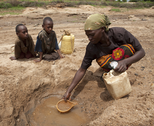 Mary draws water in Kenya from a hole she dug in a riverbank while daughters Faith (9) and Elizabeth (8) look on. Their daily journey for water takes about five hours.
