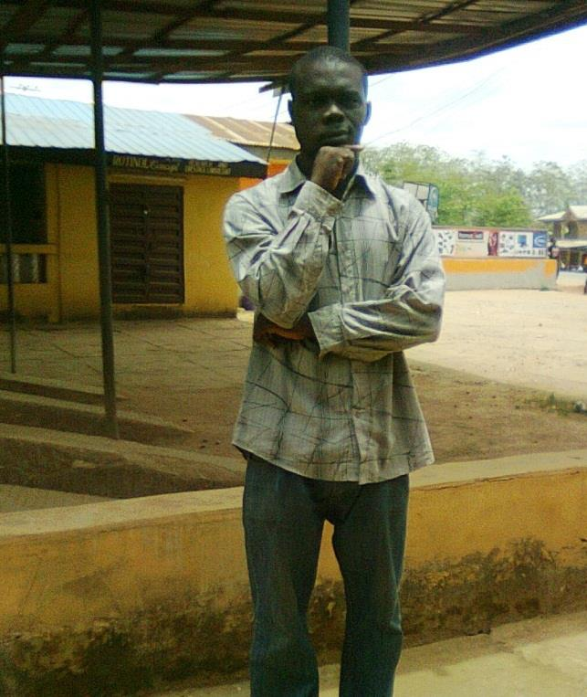 Chimezie Ihekuna (Mr. Ben) Young black man in a collared shirt and jeans standing outside under an awning in front of a small building.