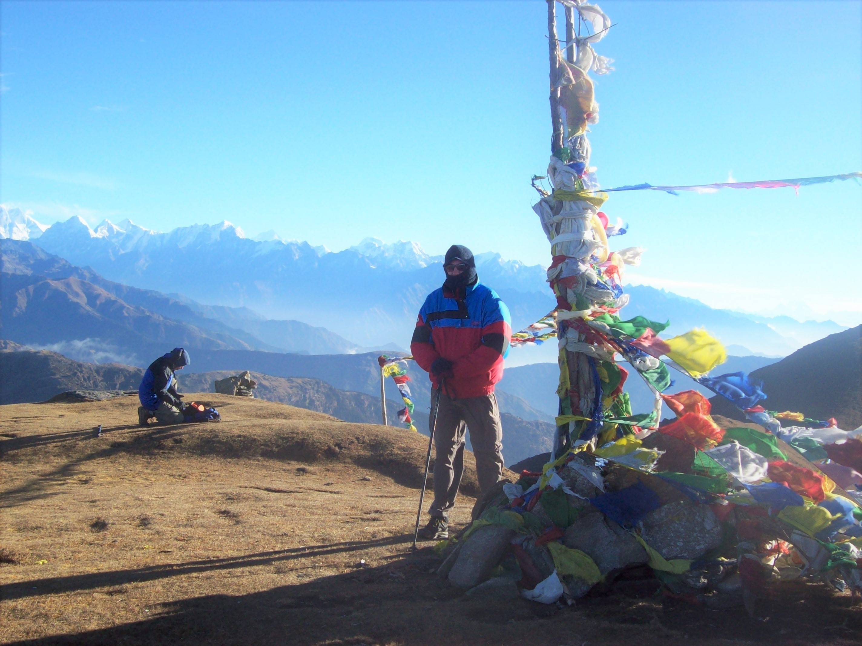 Man standing near prayer flags at a mountain summit