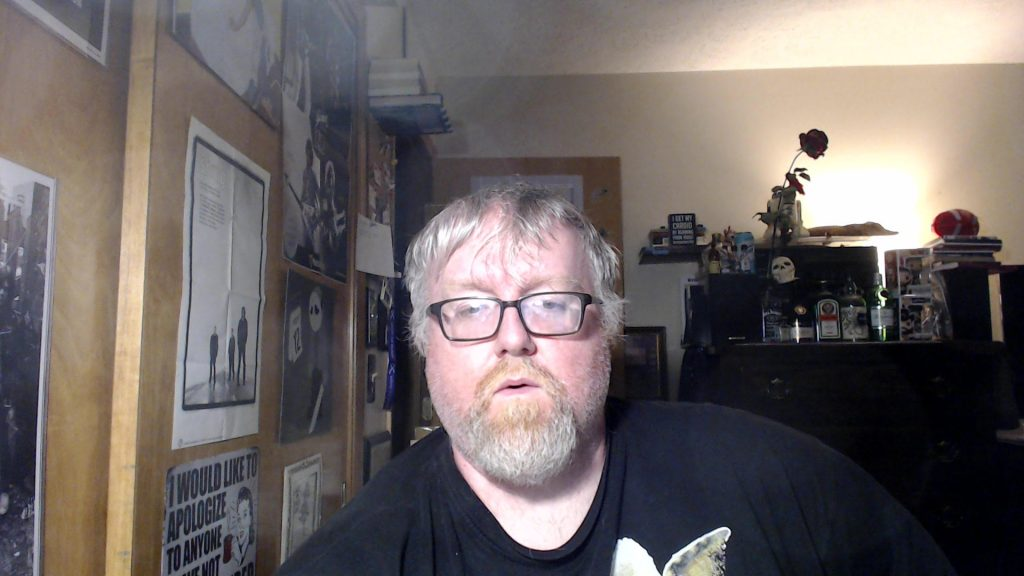 Author J.J. Campbell, white man in a tee shirt with dark-rimmed glasses, slightly messy blond hair, and a mustache and beard. In a room with a dresser with candles, a skull and a rose and posters on the side wall.