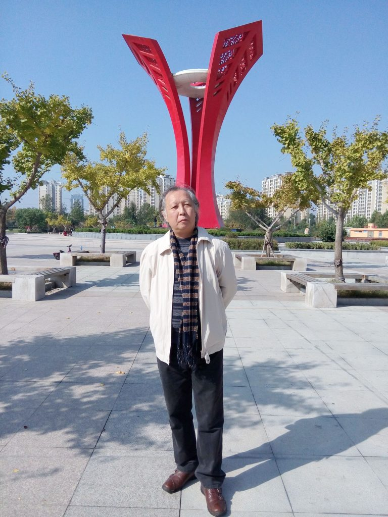 Middle aged Chinese man dressed in  slacks, brown shoes, a white coat and a scarf and striped shirt standing  in a city plaza, concrete with trees in planters.