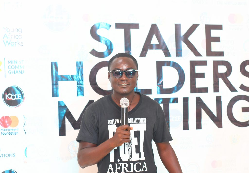 Young Black man with dark glasses holding a microphone with a tee shirt that reads 'POET' in front of a sign reading 'Stakeholders Meeting.'