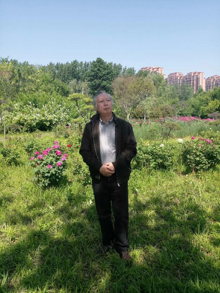 Older Asian man standing in a green field with flowers with large apartment buildings in the background