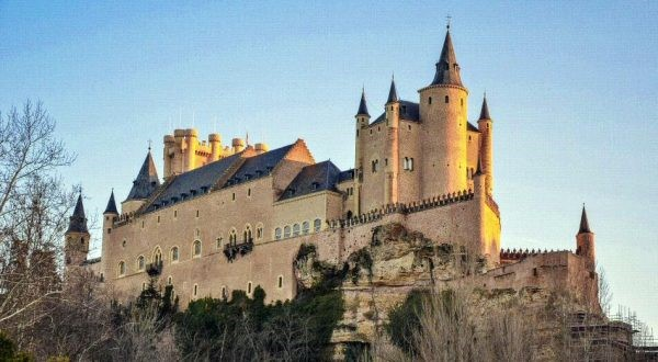 Large light brown Medieval style castle with turrets and ramparts up on a hilltop with some trees below.