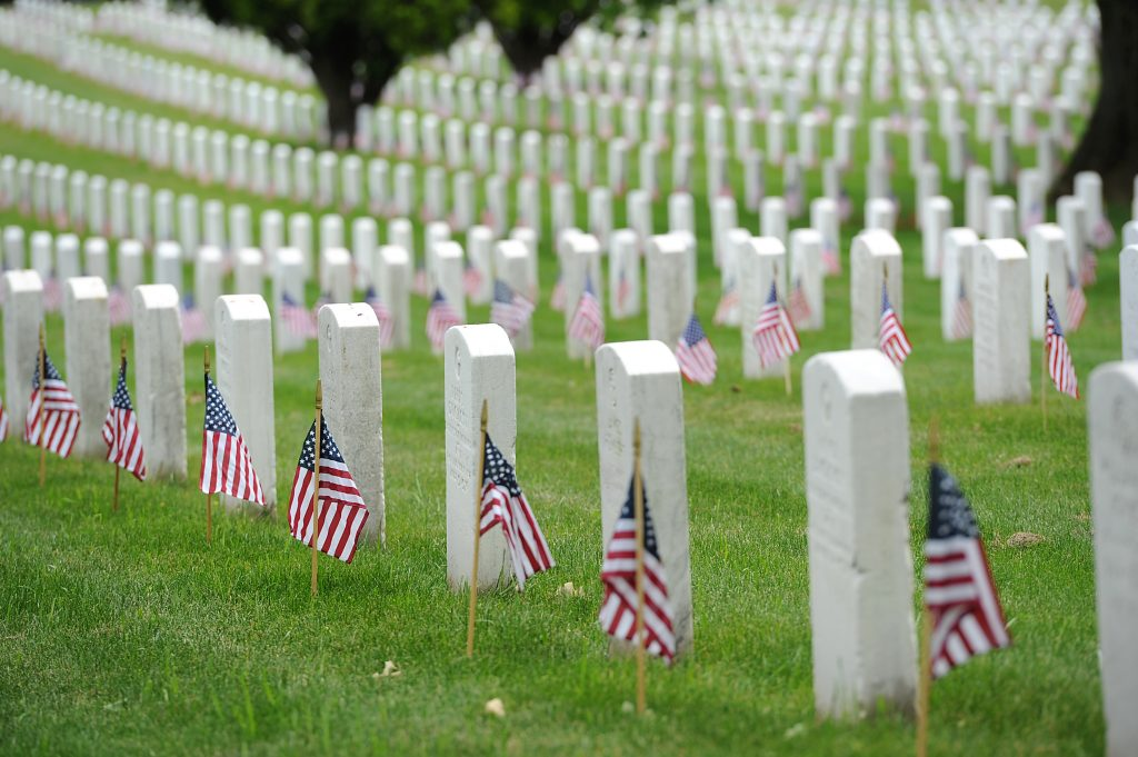 Military cemetery with flags next to rows of white tombstones.