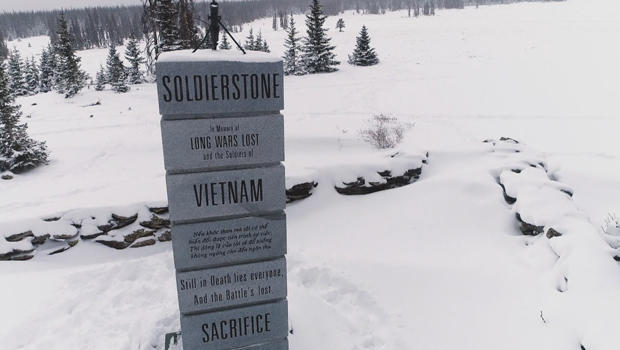 Memorial to people who died in the Vietnam War standing in a snowy field with a few evergreen trees.