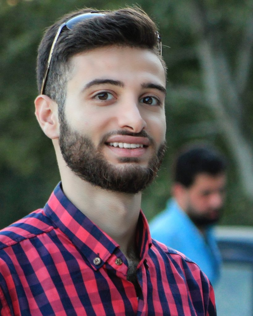 Young man with brown hair, a beard, and a collared red and blue plaid shirt