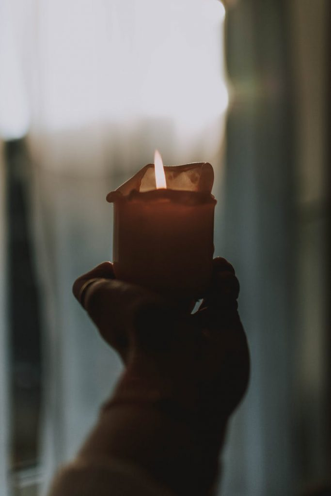Hand holding a sepia toned lit candle, soft afternoon light, indistinct background.