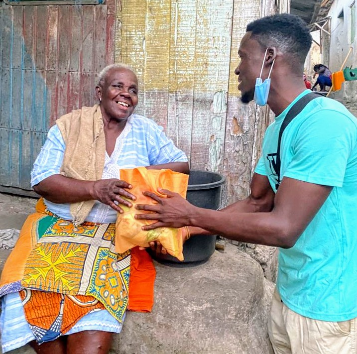 Young man, standing, handing a bag of food to an older woman seated outside on the porch of a building. She's got a colorful yellow and orange skirt.