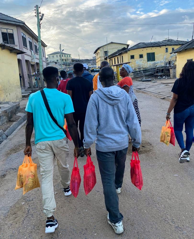 Group of young people carrying bags of food on a partly cloudy day down a street by some multistory buildings.