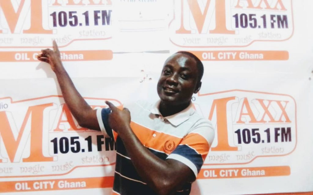 Young Black man in a striped and collared shirt stands in front of a banner for 105.1 FM Radio. His outfit, black and white and orange, matches the color of the sign.