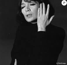 Juliette Greco singing, her eyes are half closed, she's dressed in black and her left hand is up facing her head.