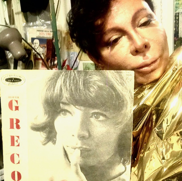 Italian man in the upper right corner with dark short hair and stage makeup and a gold shiny outfit, Juliette Greco album in the lower left corner.