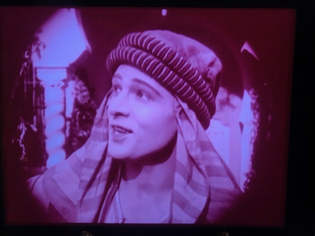 Young white man with a theatrical turban looks off to the left, facing the audience in an old black and white film still image.