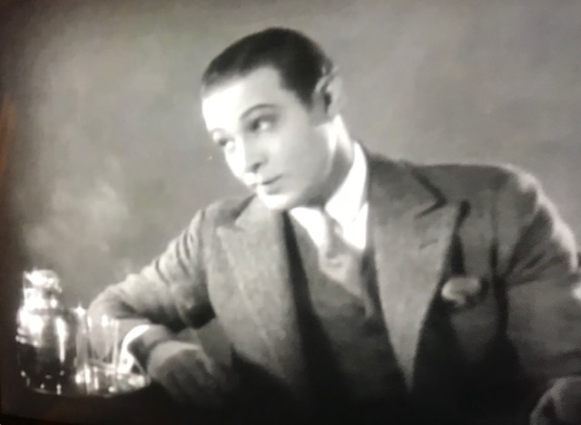 Attractive young white male 1940s movie star, slicked back dark hair and in a suit next to a tumbler of booze.