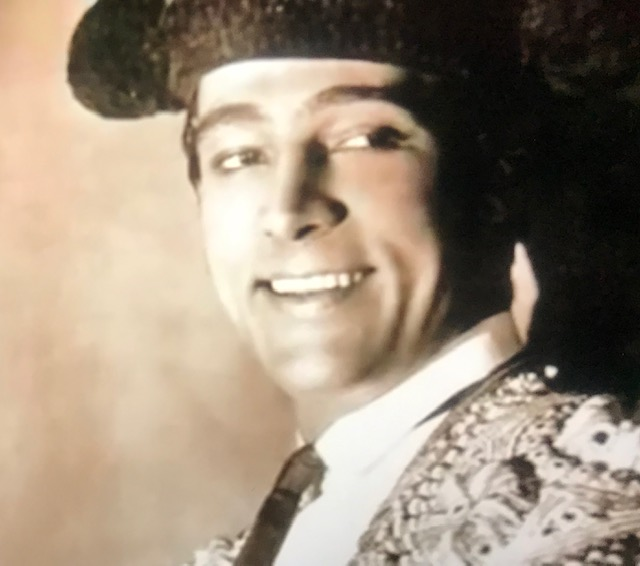 Smiling young-ish white man in a large black hat and a colorful suit, with perfectly white teeth, looking off to the right but facing the audience.