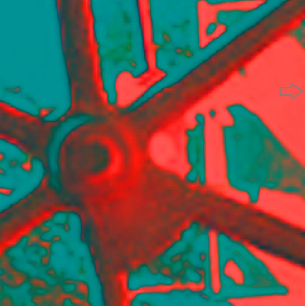 Image of a red train wheel up close, part of the wheel with the spoke off center to the left as the central focus point of the image. Background is light blue and the photo is hazy like an underdeveloped negative.