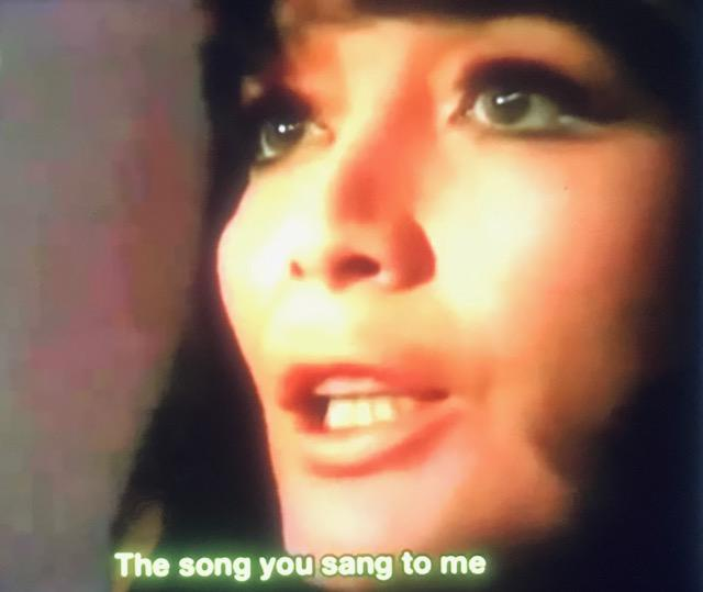 Image of a young white woman with her face turned towards the left. She's got dark hair and large eyebrows. Underneath her headshot words read The Song You Sang to Me.