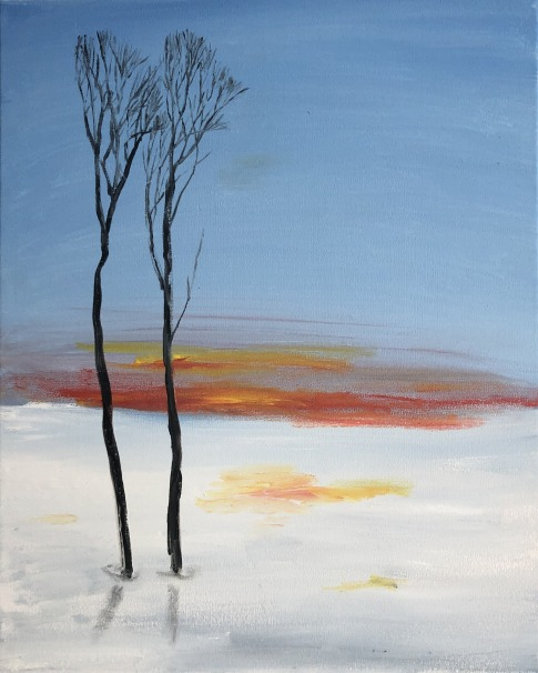 Tall leafless trees, two right next to each other, brown thin trunks in a blue pond with a red and orange sunset reflected in the water