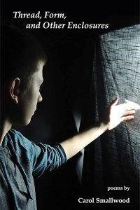White woman with short dark hair looks out through a curtain towards light outside in a dark room.