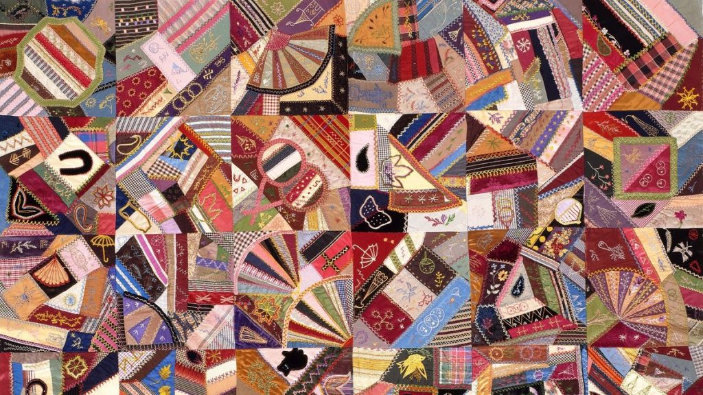 Quilt image, various kinds of fabric joined together at varying angles in a grid of squares. Pink, brown, light and dark blues, gold and yellow and pink.