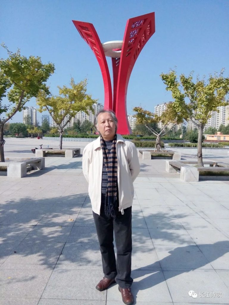 Middle aged Chinese man in a tan jacket and black pants and a scarf standing on a city sidewalk in front of some trees and a tall red sculpture