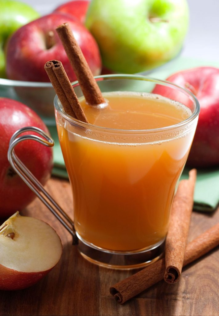 Red and green apples in the background, and then a glass mug of mulled cider with cinnamon sticks.