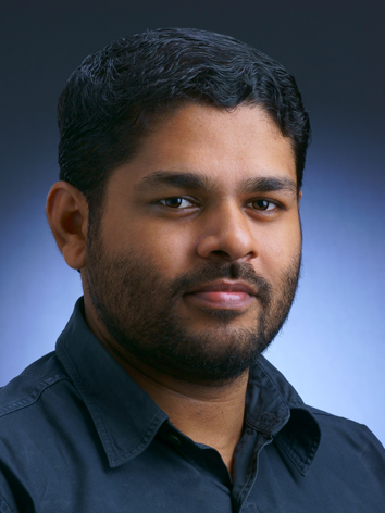 South Asian middle aged man with brown hair and a small beard. Blue collared shirt.