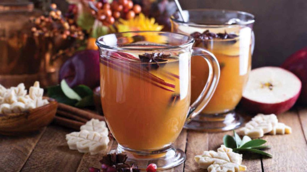 Two glass mugs with mulled cider inside, cinnamon sticks and other spice inside the mugs. Yellow flowers and tan berries are on the table next to the mugs, as are leaves, leaf-shaped cookies, and apples cut in half. Table is of brown wood.