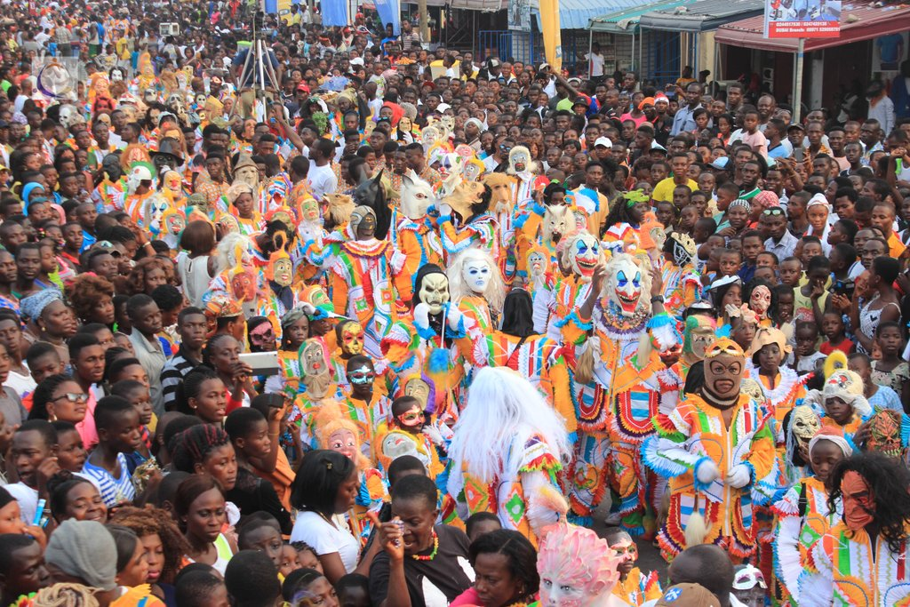 Large masquerade parade in Ghana with the people in costumes and full-face masks. Spectators in tee shirts crowd on either side to watch.