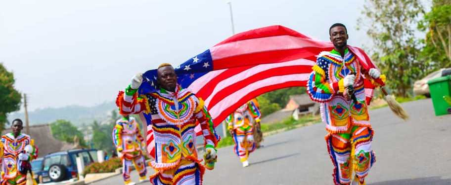 Two young Black men in the foreground carrying a large red, white and blue American flag, dressed in multicolored clothing. Others in similar getup are behind them, on the road in a suburban street.