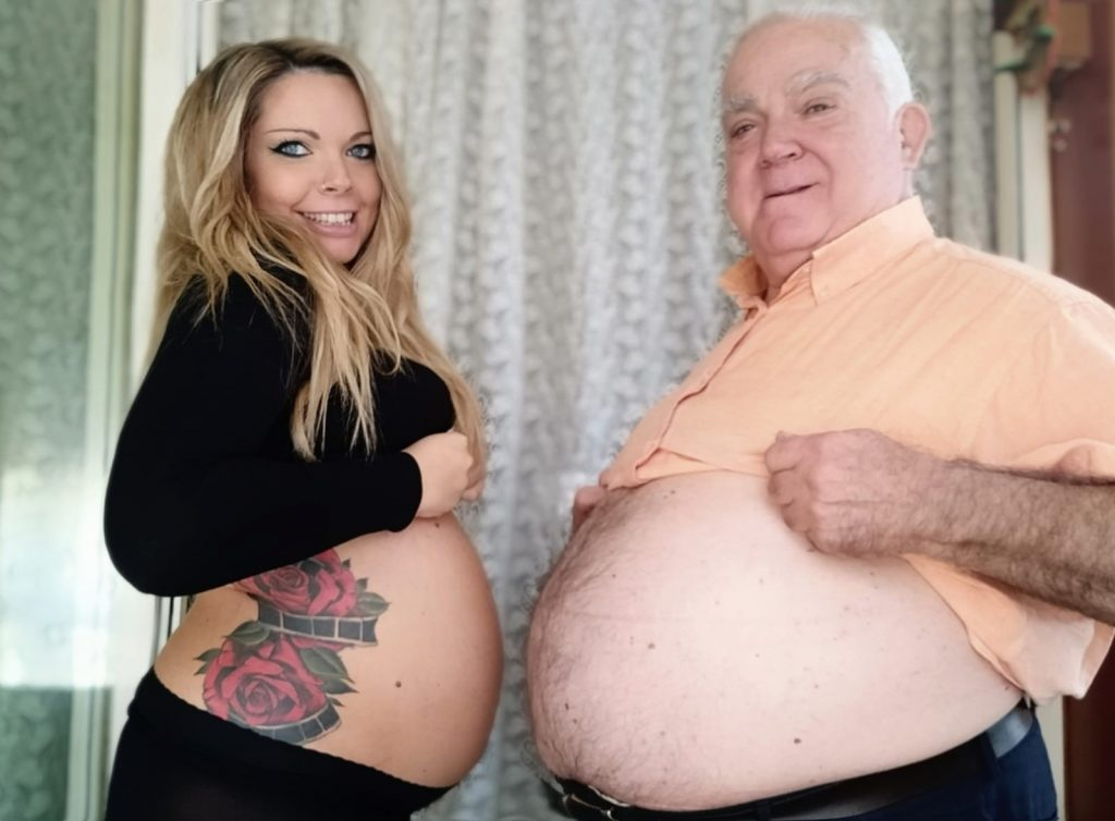Older white man with thinning hair, a light orange collared shirt and a large chubby belly, uncovered. Next to him is a young white woman, with a black top and black pants. She has also uncovered her pregnant belly and has a tattoo on her side of red roses and what looks like film reels.