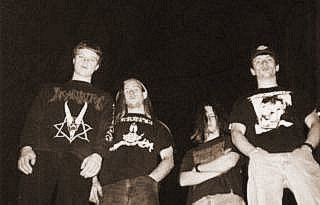 Group of young white guys posing for a black and white photo. They all have tee shirts and jeans, one has a pentagram and the others have different designs. One has a baseball cap.