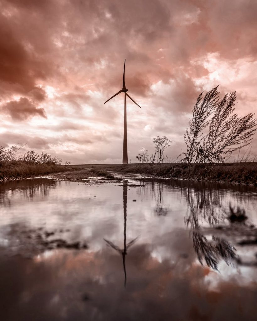 Single windmill in a wet marsh area with water and some windswept grassy plants, clouds overhead and a pink/purple sunset or sunrise color.
