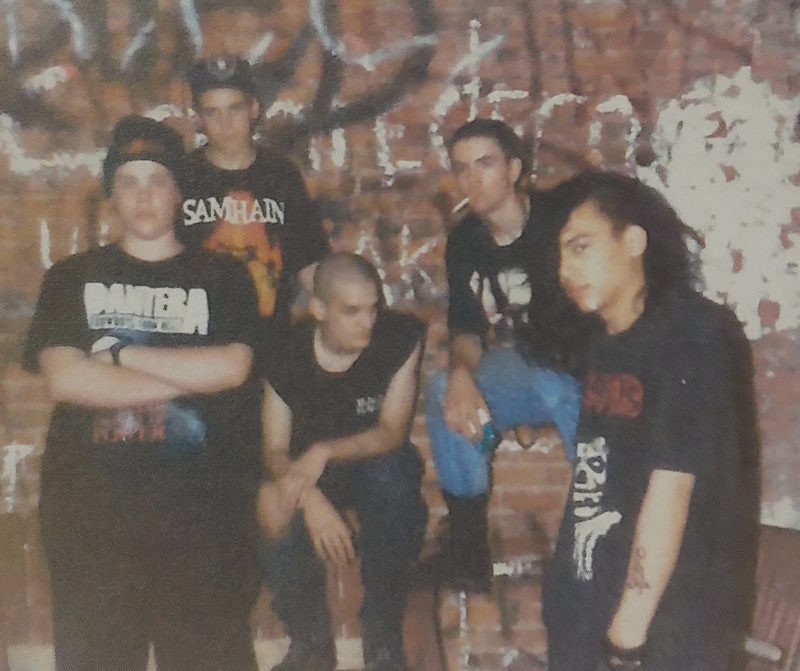 Five guys, some white and some of indeterminate race, with black tee shirts with heavy metal band logos, posing in front of a brick wall with graffiti.
