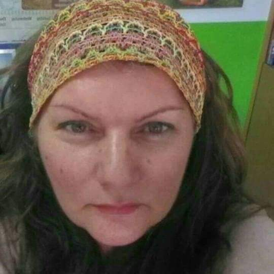 Middle aged white woman's headshot, she has a multicolored patterned scarf on her head and dark hair.