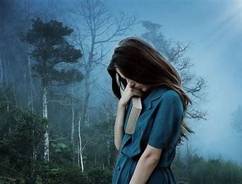 White woman with dark hair and a blue dress bent over in thought, with a book under her arm. She's in a misty forest with some trees which have leaves and others which don't.