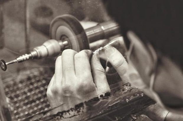 Person holds beads on a bracelet over a refining tool to polish them, in a black and white sepia photo.