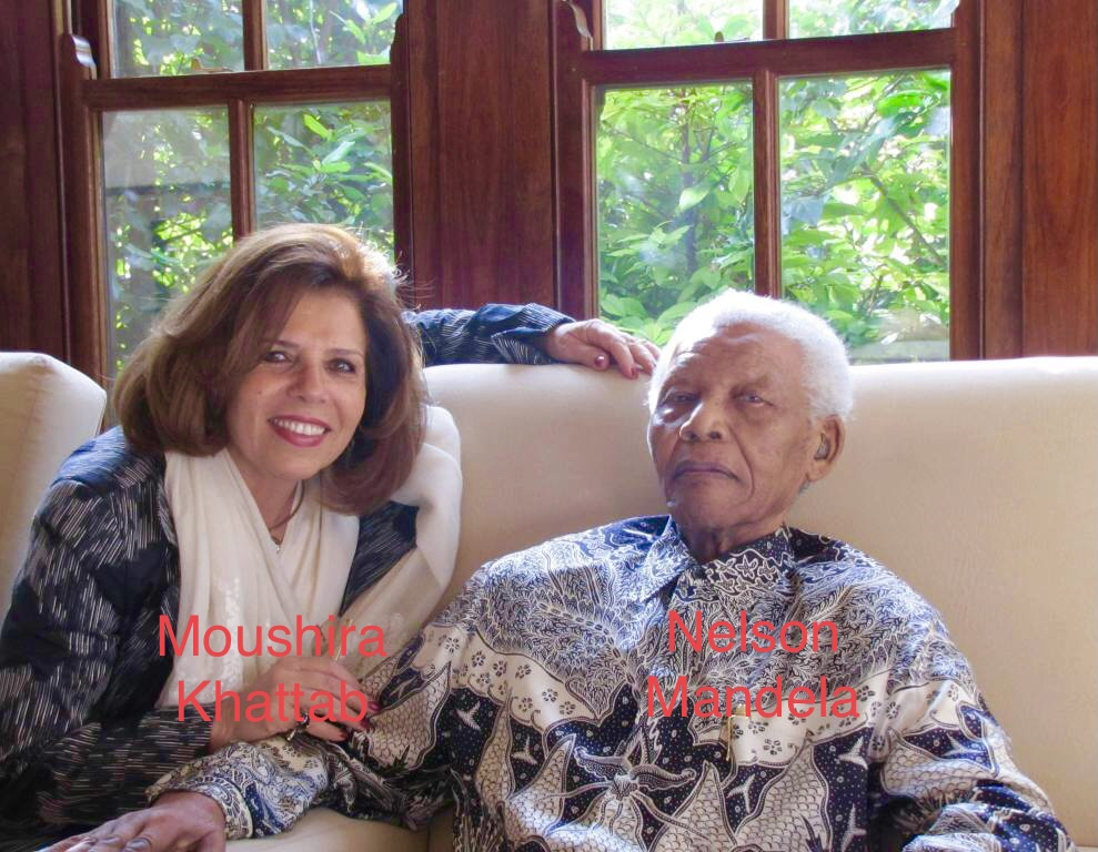 Light-skinned middle aged woman with brown shoulder-length hair sits on a white couch in a living room with windows and green plants outside. She's wearing a white scarf and patterned blue and white top. Nelson Mandela, a white haired Black man, sits next to her and is in a blue and black and white patterned collared shirt.
