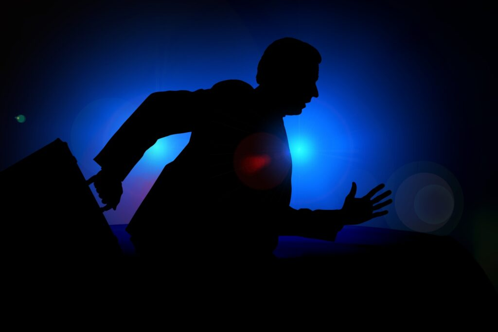 Nondescript shadowy male figure running against a blue and black background carrying a briefcase in his right hand.