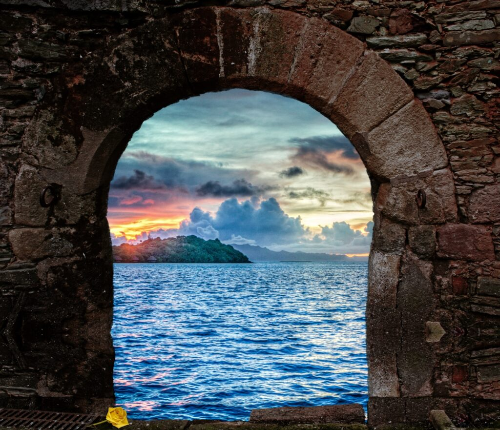 Arched opening in a brick wall opens to a view of a large body of water with clouds and a sunrise/sunset in the background. A green island looms in the distance.