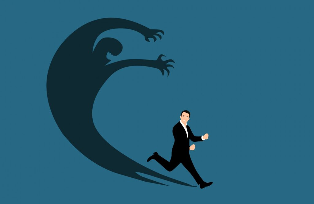 Nondescript clip art white male figure in a business suit runs from his shadow, which has grown and morphed into a menacing creature with teeth and claws.