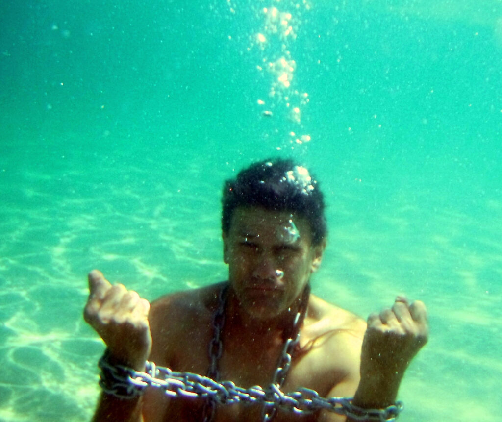 White or Latino man with short brown hair (real image of a person) with chains around his neck and hands underwater. Part of an escape stunt game.