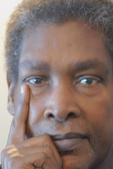 Middle aged Black man with short hair and brown eyes. He's got a hand on his chin and is facing the camera.